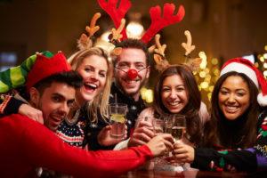 Anstoßen in witzigen Weihnachtskostümen auf der Party