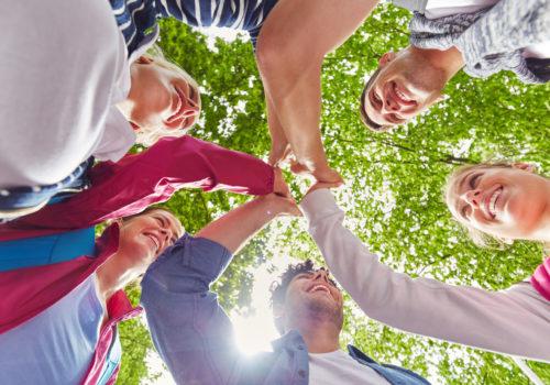 Team gratuliert sich mit High Five für die erfolgreiche Zusammenarbeit