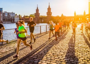 Group of female and male runners jogging in urban area at sunset