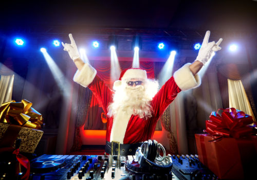 DJ Santa Claus mixing up some Christmas event. Disco light around fun, colorful atmosphere. Musical New Year.