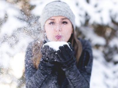 Frau pustet Schnee von der Hand