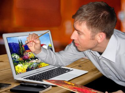 Mann malt auf Laptop