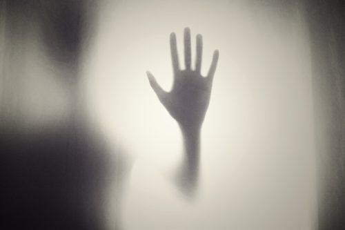 Hand hinter Schattenwand